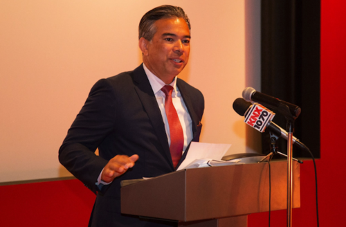 Rob Bonta in dark grey suit with red tie behind brown podium and in front of brown wall