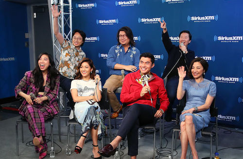 """""""Crazy Rich Asians"""" cast and author in multicolored clothing on black chairs and stools on grey floor and in front of blue wall with white text"""