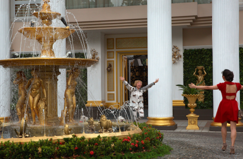 Large gold fountain in front of white, tan and gold house with massive white columns. Two women walk toward each other, arms above their heads