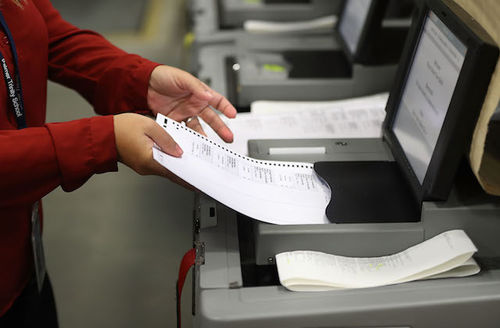 arms in red sleeves insert ballot into voting machine