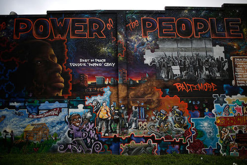 A spray painted mural on a brick wall depicts Freddie Gray