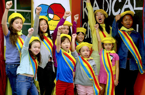 Kristina Wong and girls in yellow hats and rainbow sashes raising fists in front of white and blue and red walls and art