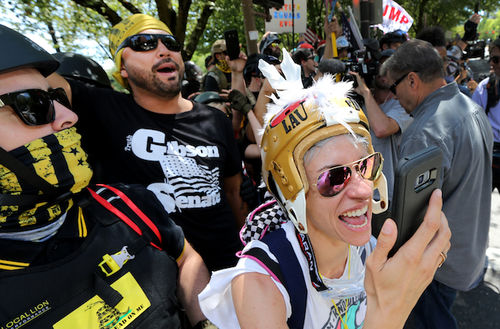 Joey Gibson: A White with a beard wearing his campaign t-shirt cheers