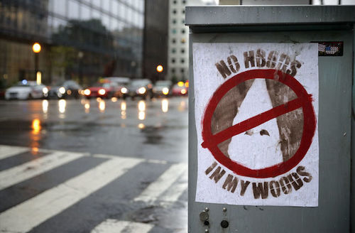 """White sign with KKK hood with a no sign over it and brown text that reads, """"No hoods in my woods."""""""
