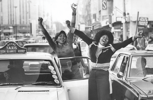 Archival image of Black South African women with black afros holding hands in air and smiling near taxi cabs in front of buildings