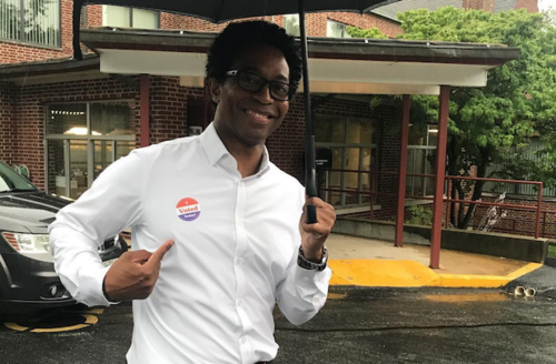 """Wesley Bell. Black man smiles and points at his """"I voted"""" sticker."""