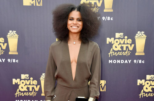 Zazie Beetz with black afro in green dress in front of dark grey wall with gold images and text