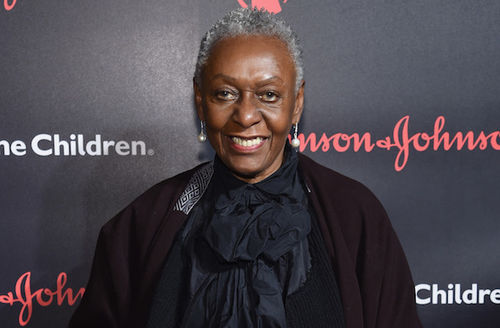 Bethann Hardison in black sweater and scarf in front of black wall with white and red text