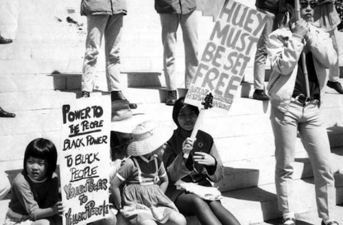 Black and white photograph of two Asian-American girls and an Asian-American woman holding signs while sitting on building steps