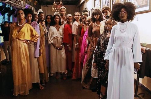 Black women pose in multicolored attire on brown carpet in front of brown ceiling and blue and grey walls