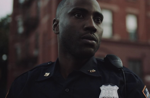 John David Washington. Black man in navy police uniform in front of grey sky and red brick building