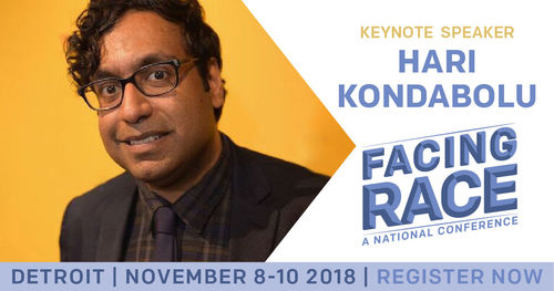 Hari Kondabolu stands in front of an orange step-and-repeat wearing glasses, a dark plaid shirt, and black jacket and tie. With Facing Race
