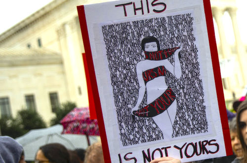 """A drawing of a black and white body wrapped in red ribbon that says """"This is not yours"""""""