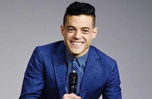 Rami Malek in blue suit and dress shirt holding black microphone in front of grey wall