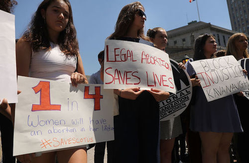 """Protesters outside hold signs, including some that say, """"Legal abortion saves lives,"""" """"Block Injustice Kavanaugh,"""""""
