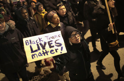 "Protesters outside at night, one holds sign that reads, ""Black trans lives matter."""