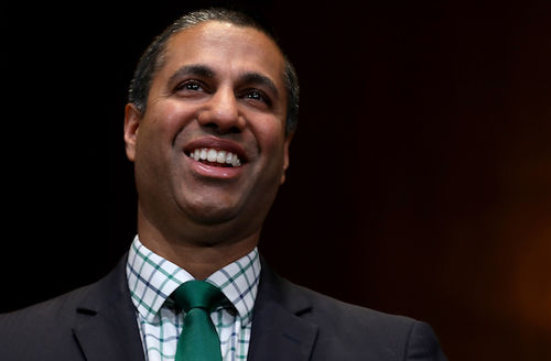Ajit Pai. Desi man in black suit with green tie smiles in front of black background