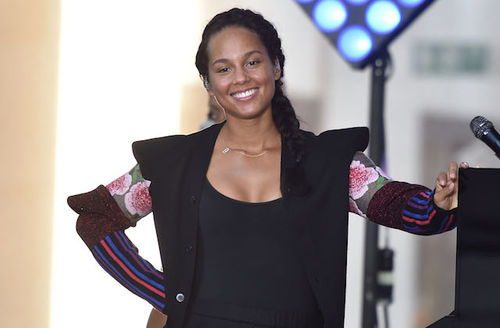 Alicia Keys. Black woman in black shirt and blouse with pink flowers and blue and red lines on sleeves smiles while holding onto black piano in front of black light stand and blue lights and brown building