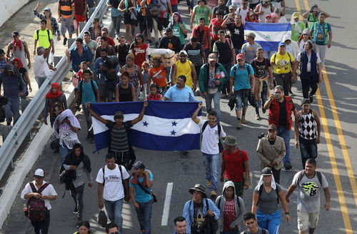 Members of the migrant caravan carry flags from Honduras (L) and Nicaragua (R), while crossing the Guatemalan border into Mexico, near Ciudad Hidalgo, Mexico on October 21, 2018.
