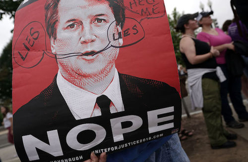 """A demonstrator holds up a red, black and white poster that reads """"Nope."""""""