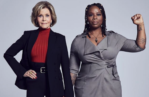 Jane Fonda and Patrisse Khan-Cullors. White woman in navy suit and red sweater holds hands with Black woman in grey dress with black arm tattoos and raised fist, in front of grey background