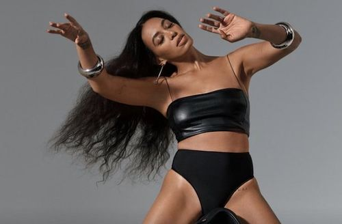 Solange. Black woman in black leather two-piece outfit with arms in air in front of grey wall
