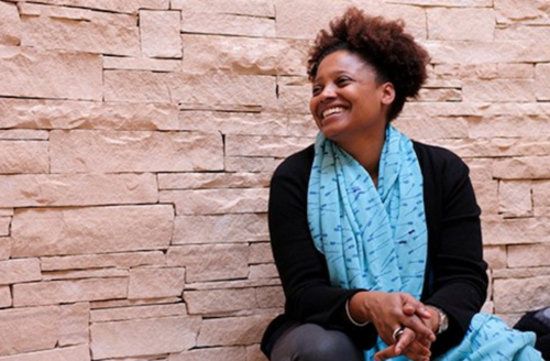 Tracy K. Smith. Black woman in black sweater and blue scarf and grey pants in front of brown brick wall