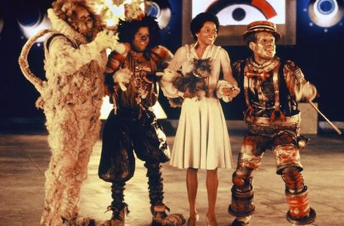 Ted Ross, Michael Jackson, Diana Ross, Nipsey Russell. Black woman and man in multicolored costumes stand in front of navy blue wall and brown wood floor as woman holds grey dog