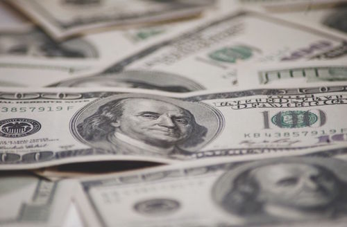 A 100 dollar bills out of focus layinf on top of each other with one 10 dollar bill in the forefront in focus