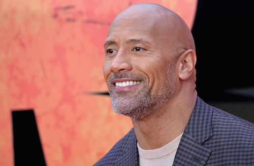 "Dwayne ""The Rock"" Johnson. Black man with grey goatee smiles while wearing brown shirt and blue and black checkered blazer in front of orange and black background"