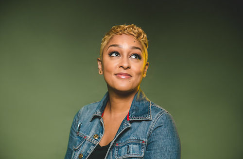 Eve Ewing. Black woman with short blonde hair in black shirt and blue jean jacket with red accents in front of green background