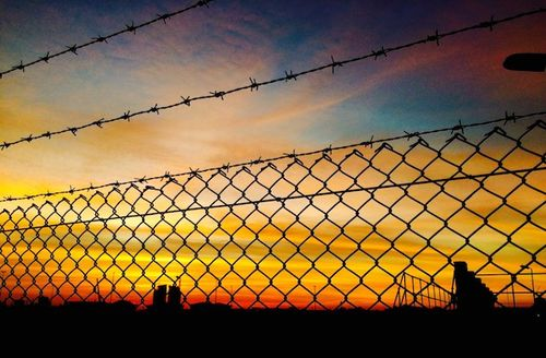 Barbed wire surrounding a prison during sunset.
