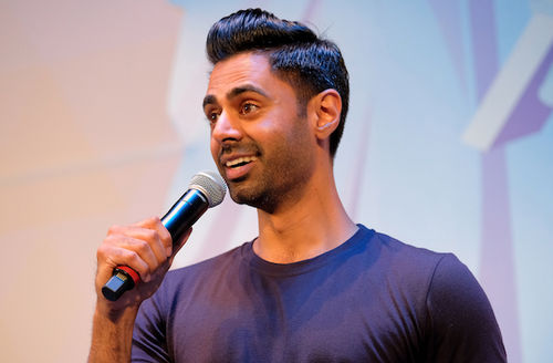 Hasan Minhaj. Brown man with black hair and beard smiles while holding black and grey microphone and wearing blue shirt in front of purple and blue and orange screen