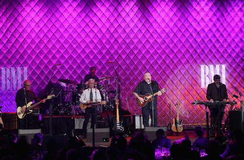 Los Lobos. Mexican-American men in black and white dress clothing hold guitars and other instruments in front of purple background