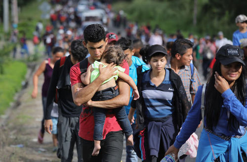 Large group of Hondurans march north as part of mass migration march. Young man wearing red shirt holds a small child and is surrounded by women and men as hey walk on a Central American road.