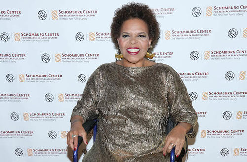 Ntozake Shange. Black woman with short, curly brown hair smiles in gold dress and blue wheelchair in front of white screen with brown and yellow logos and text