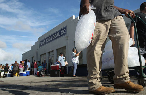 "Black people stand in line outside gray building that reads ""Rose ice and coal co."" Black man in foreground holds bag of ice."