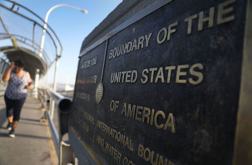 "Image of bronze plaque against a blue sky with a blurred person in a patterned top and dark capris in the background; it reads ""Boundary of the United States of America."""