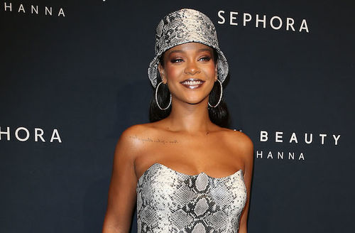 Rihanna. black woman in grey snakeskin dress and black tattoo on collarbone smiles in front of dark navy wall with grey text