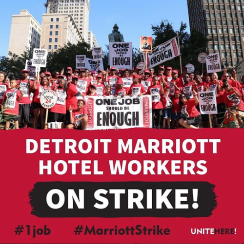"""Detroit hotel workers and their families holding picket signs reading """"One Job Should Be Enough"""""""