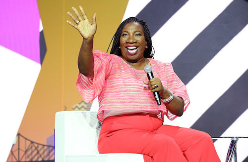 Tarana Burke. Black woman with black dredlocs in pink shirt and pants waves and holds black microphone while sitting on white chair in front of black and white and gold and purple background
