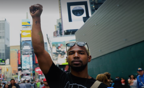 A Black man with blonde hair wearing sunglasses on his head raises a power fist at a rally in Midtown Manhattan