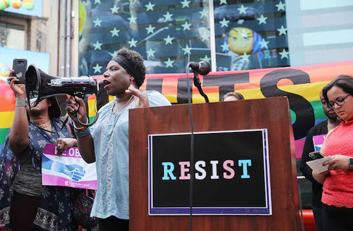 """Tanya Walker. Black transgender activist holds black megaphone while wearing grey shirt behind brown podium with pink and light blue transgender transgender pride flag with letters reading """"RESIST"""" and surrounded by other people with multicolored signs"""