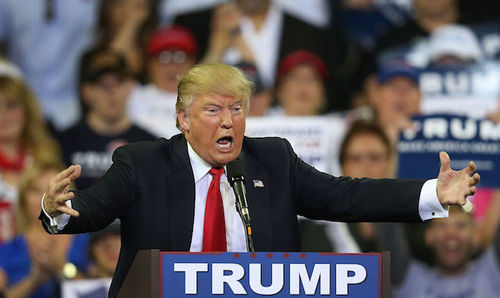 """Donald Trump: A White man in a blue suit and red tie grimaces and gesticulates behind a podium that says """"Trump""""."""