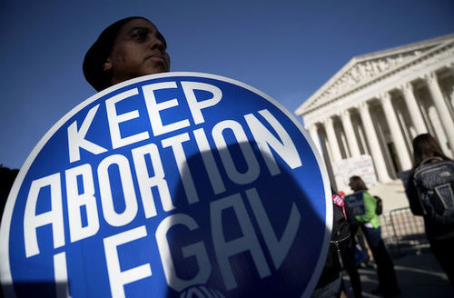 A Black protestor holds a sign that says 'keep abortion legal' in front of the supreme court