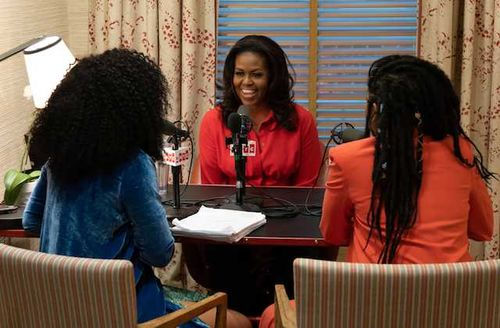 Phoebe Robinson, Michelle Obama and Jessica Williams. Black women in blue and orange outfits sit facing Black woman in red shirt around black and brown table with black and red and white microphones in front of brown wall and shade
