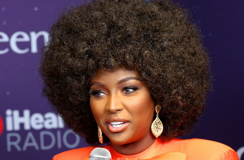Amara La Negra. Black woman with brown afro in orange outfit smiles while holding microphone with grey cover in front of purple background with light blue text