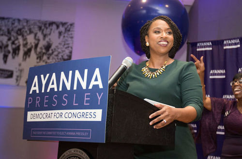 "Ayanna Pressley. Black woman in green dress stands behind wooden podium with sign that says, ""Ayanna Pressley Democrat for Congress."""