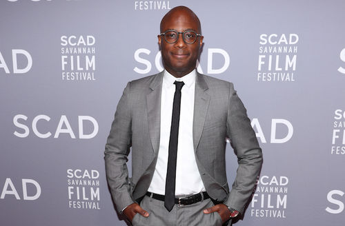 "Barry Jenkins. Black man in grey suit and glasses smiles in front of grey wall with white text reading ""SCAD"" and ""SCAD SAVANNAH FILM FESTIVAL"""