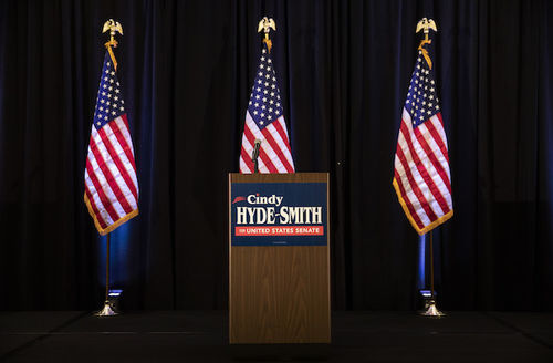 """Stage with brown wood laminate podium, red, white and blue sign on it reads """"Cindy Hyde-Smith for United States Senate."""" Three American flags on poles behind it."""